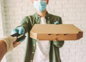 Hipster guy delivery service worker in medical face mask and gloves hold pizza box in hand, checkout customer with credit card