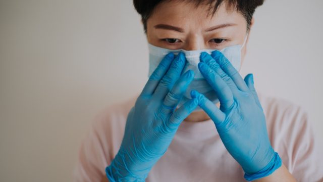 a female with her latex surgical glove wearing her face mask before going out