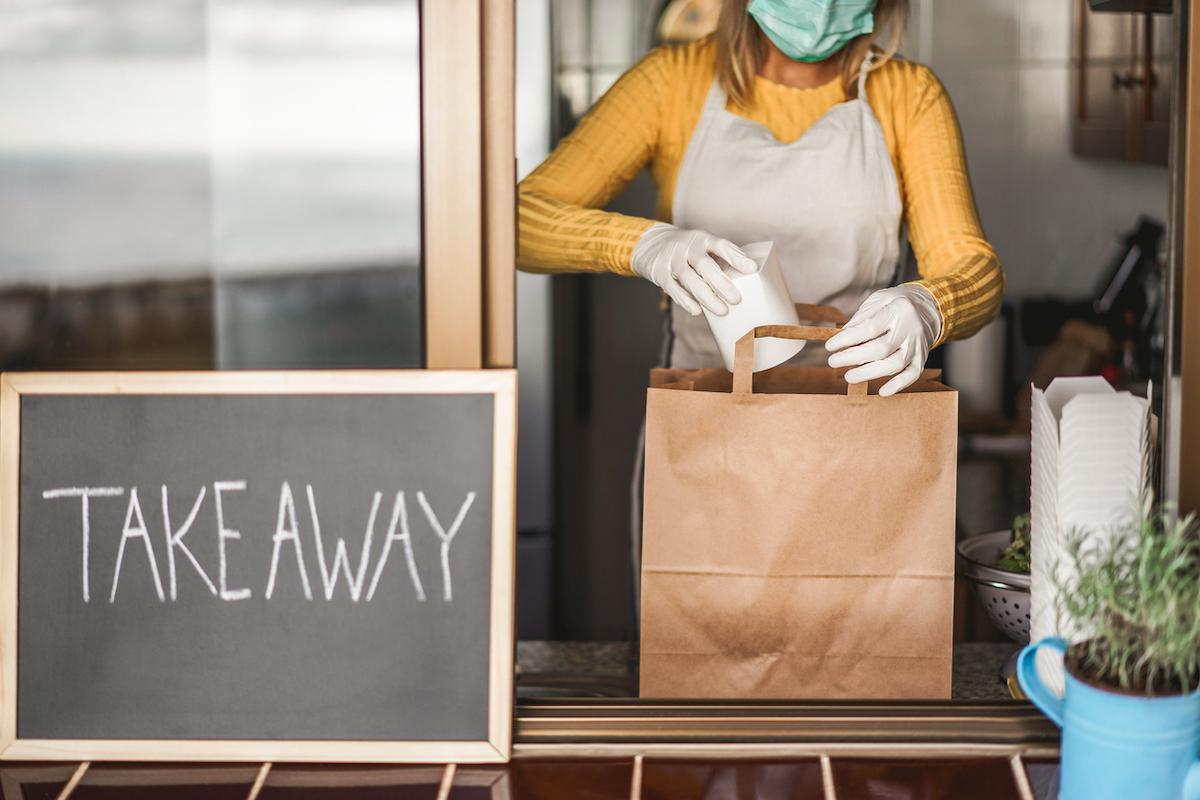 Young woman preparing takeaway food inside restaurant during Coronavirus