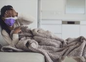 Young ill woman holding hand on forehead, checking temperature, resting, lying on the couch with a cozy blanket. Using purple face mask to prevent other people from getting infected.