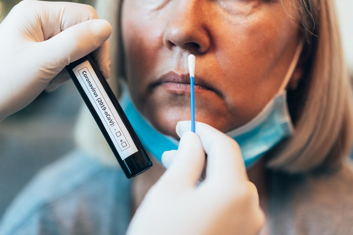 Doctor's hands in protection gloves holds Testing Kit for the coronavirus test