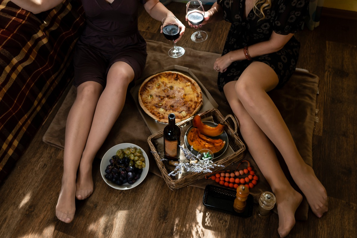 two women eating pizza and drinking wine on indoor picnic date