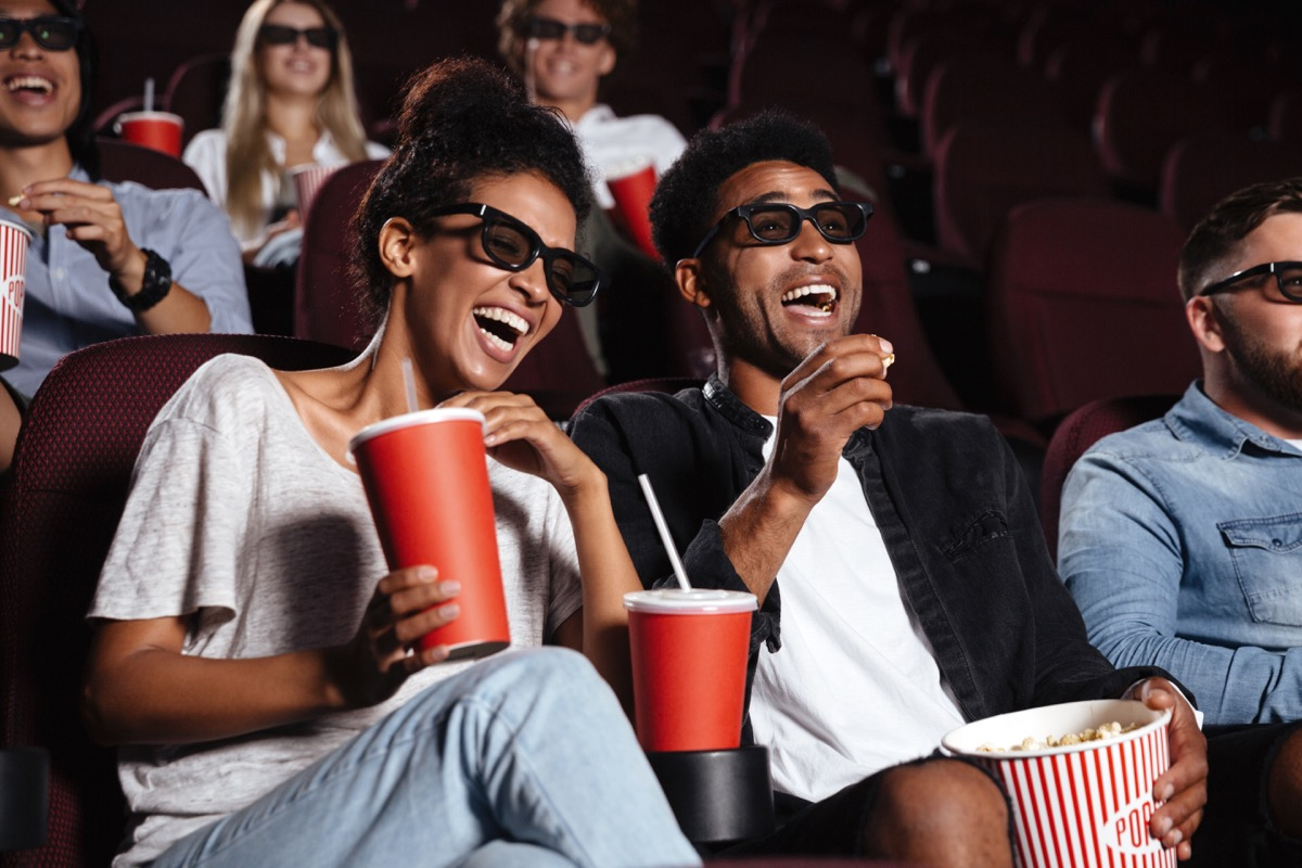 young black couple in movie theater laughing while watching a movie