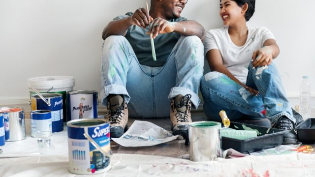 a man and woman paint walls together