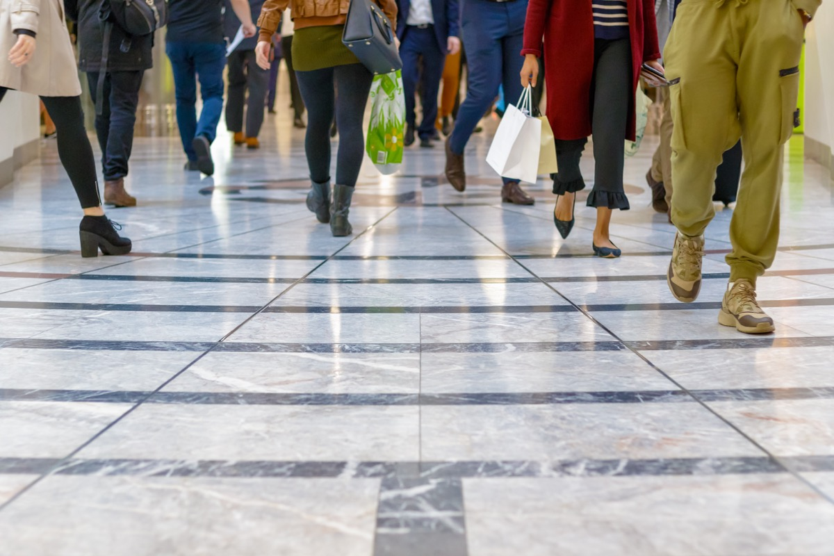 A modern floor with legs of a crowd walking in a shopping mall in the background