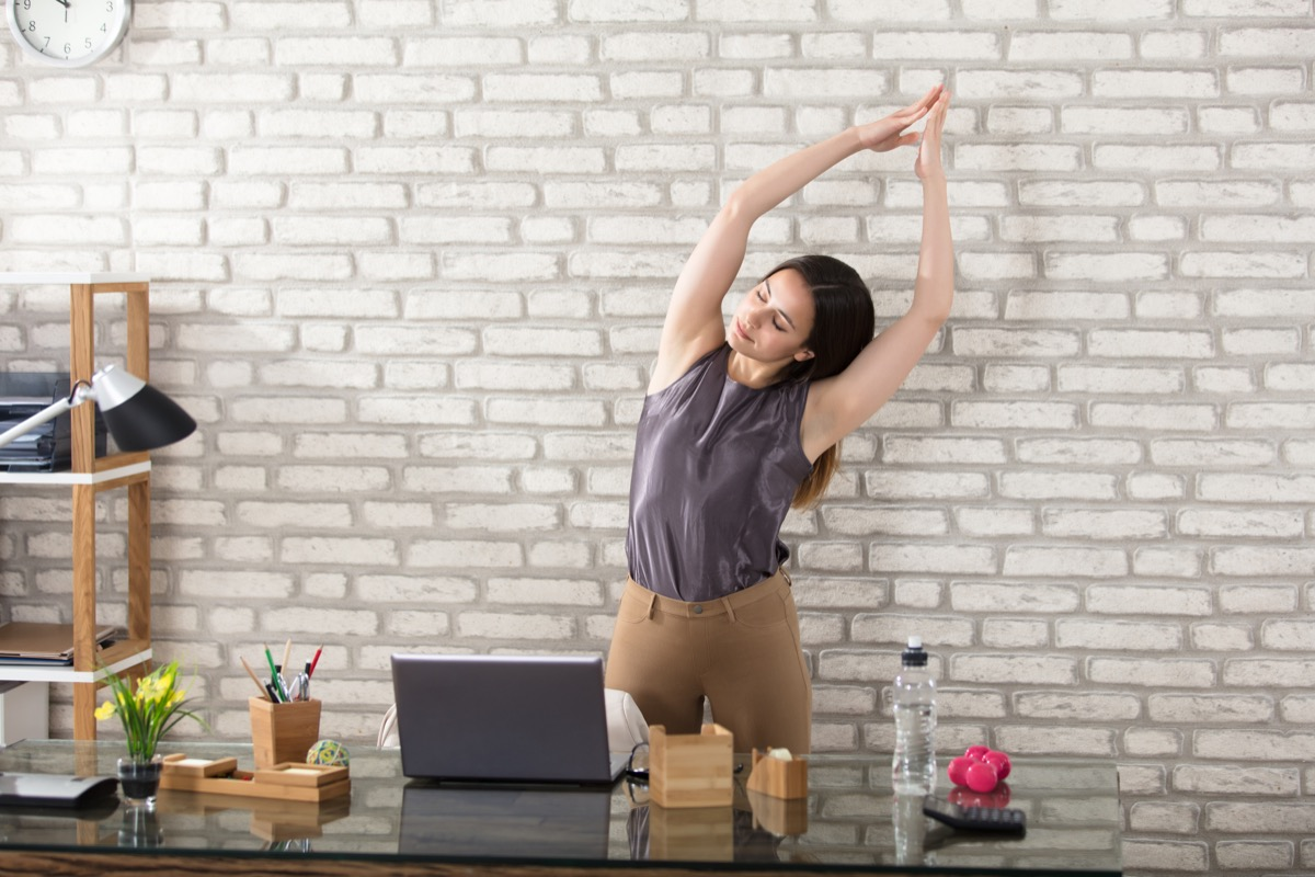 Woman stretching at her desk