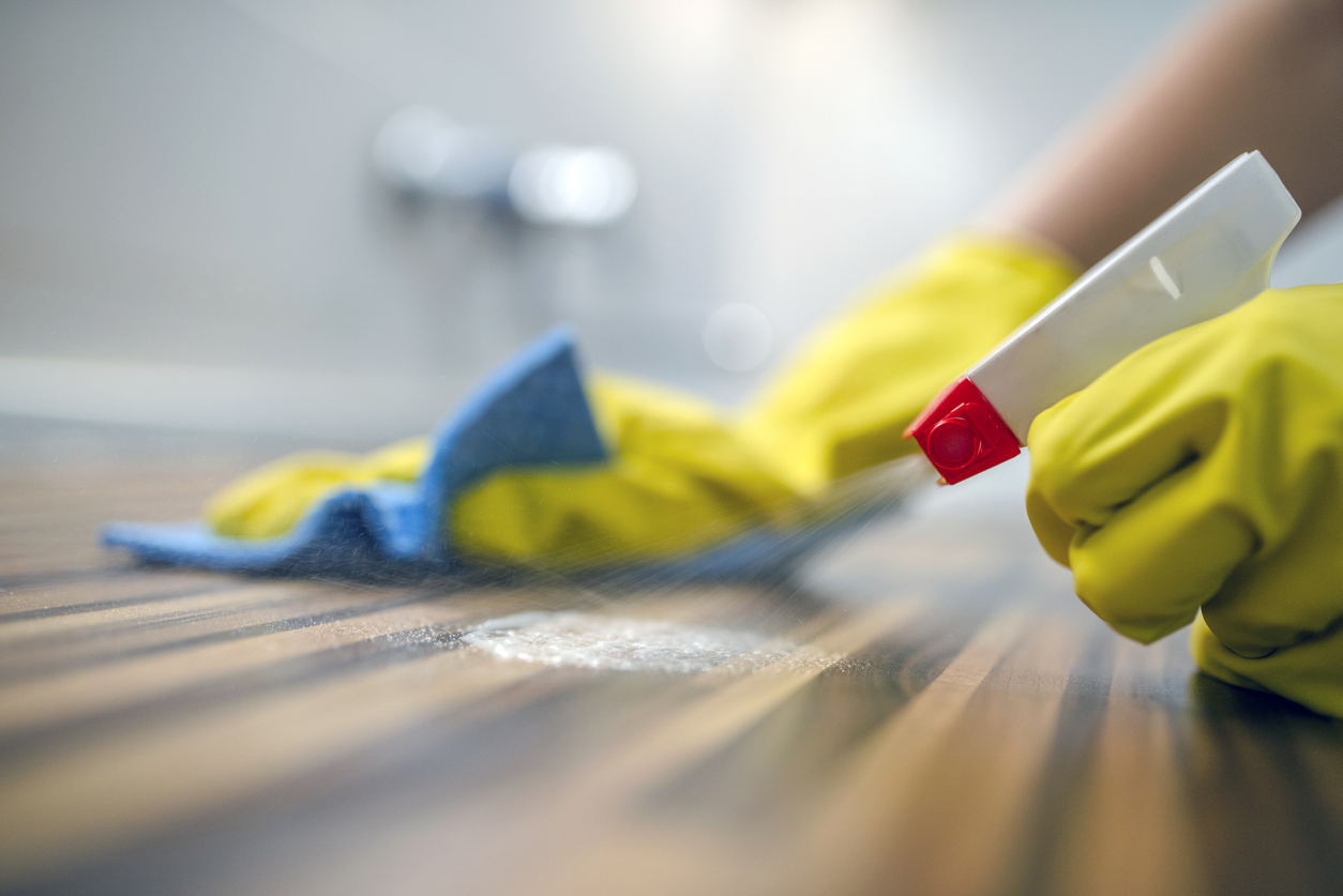 closeup of hand cleaning kitchen counter with sponge and spray disinfectant