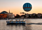 Panoramic view of Disney Springs and water taxi on colorful sunset background at Lake Buena Vista area
