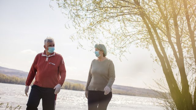 Senior couple walking trough nature with mask on face.