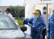 healthcare employee doing covid-19 testing at drive-through
