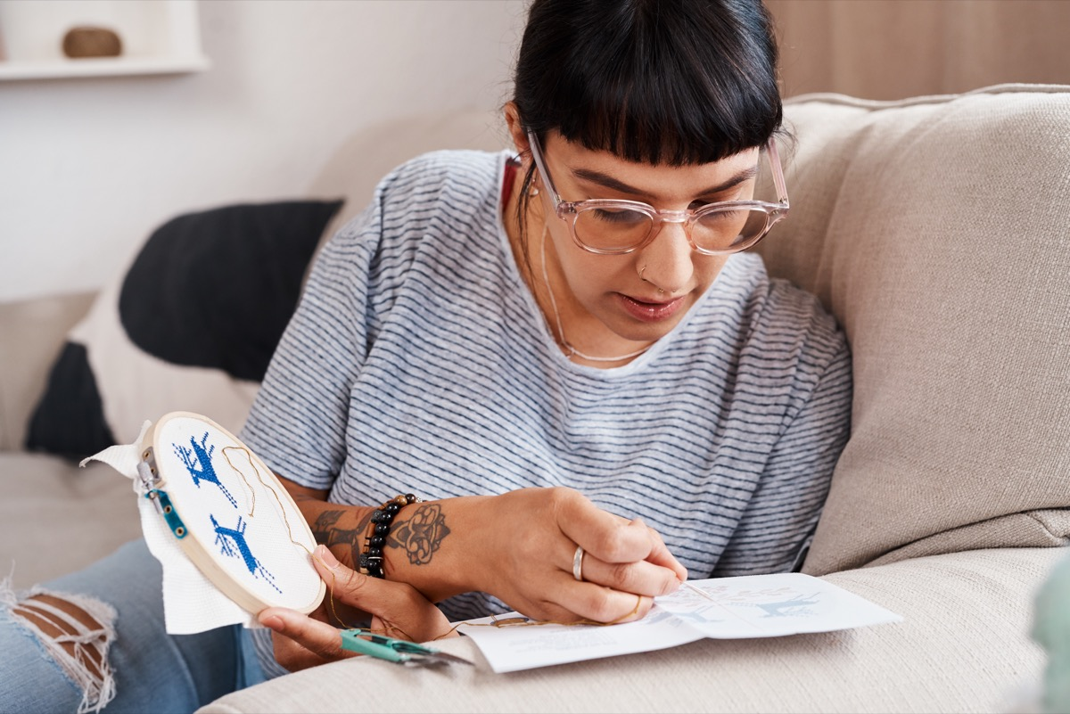 Shot of a beautiful young woman doing embroidery at home
