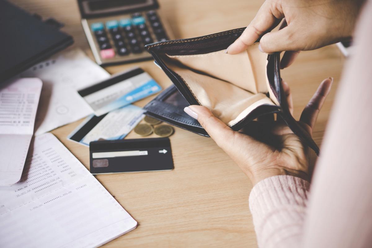 woman emptying wallet onto desk