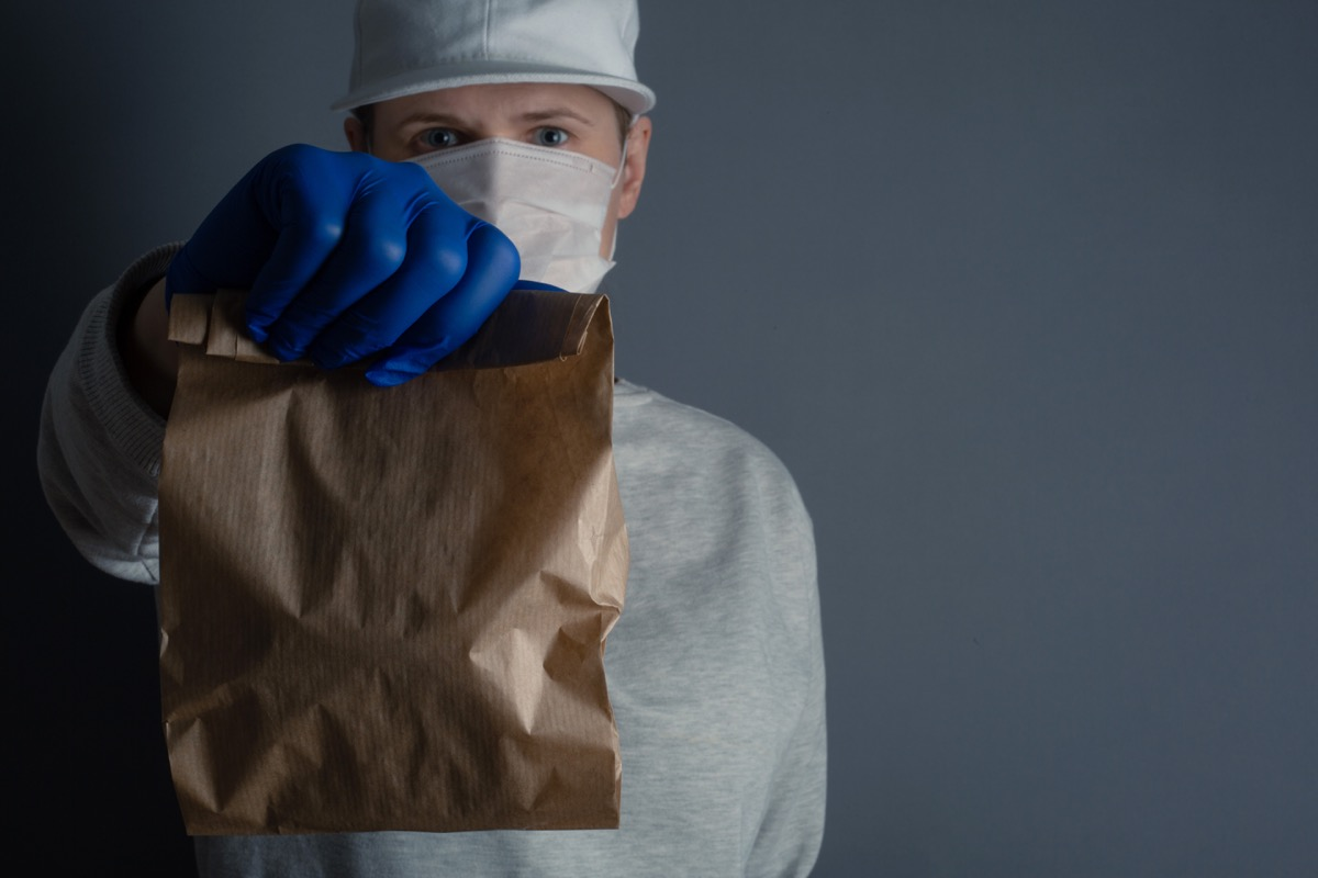 man holds a brown lunch bag