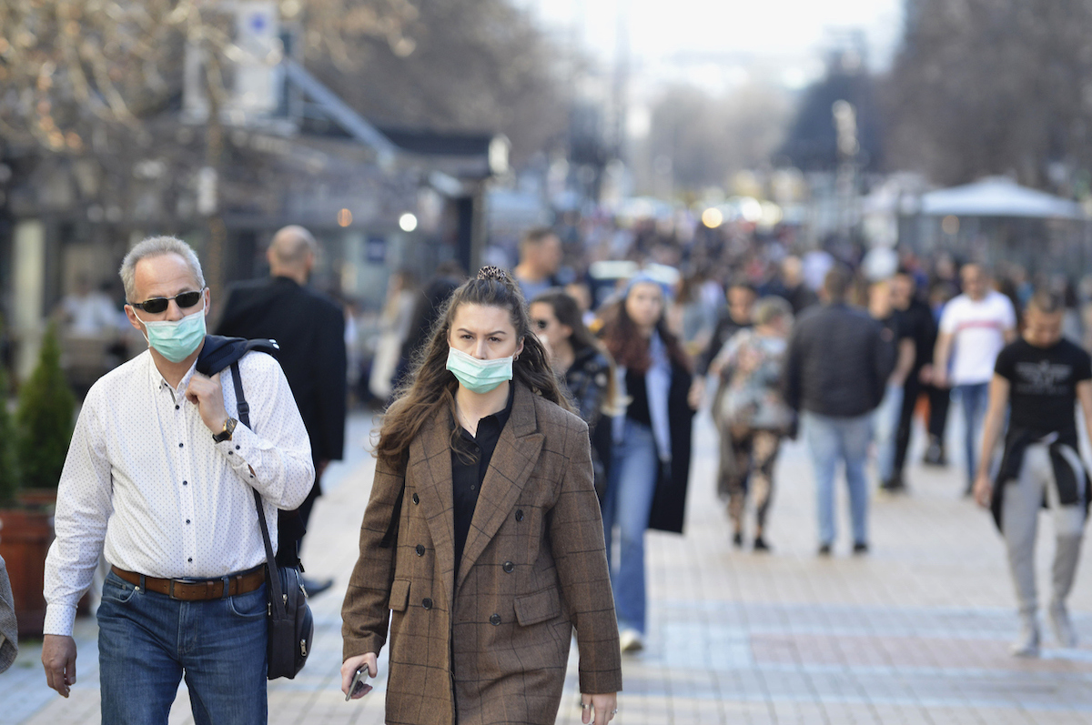 A young woman and an older man are walking on street wearing face masks while others are not