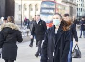 Young woman wearing face mask while walking in the streets of London