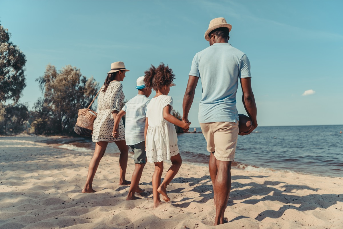 young black family walking on beach