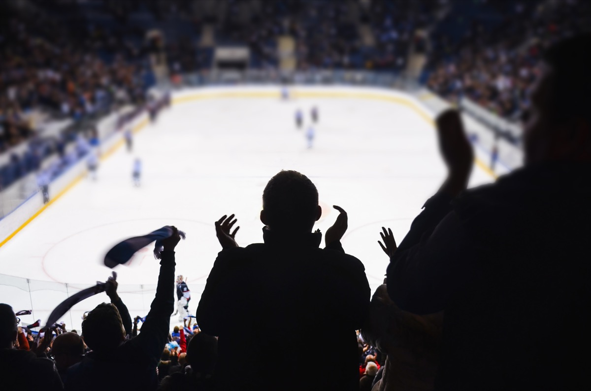 fans cheering ice hockey game at sports venue