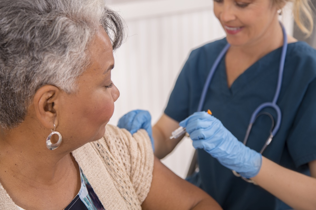 Nurse gives flu vaccine to senior adult patient at a local pharmacy, clinic, or doctor's office.