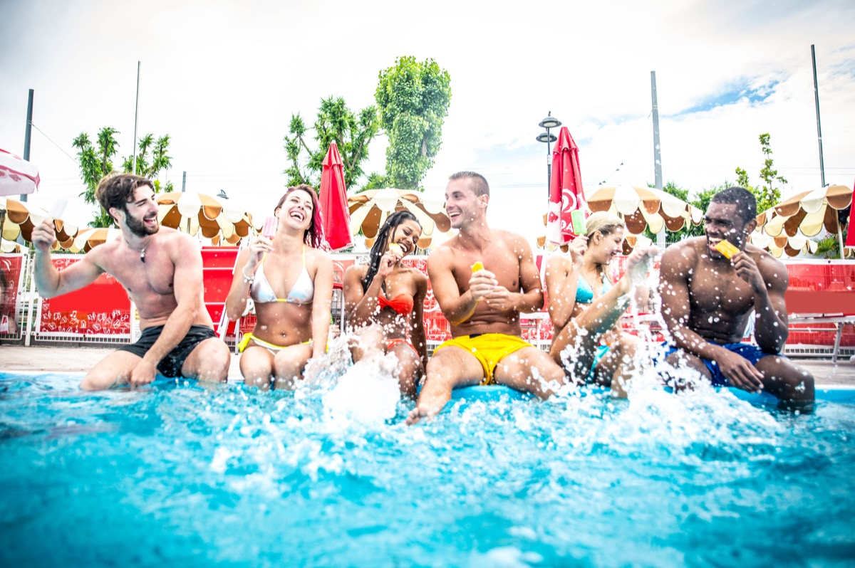 young multi ethnic friends having pool party