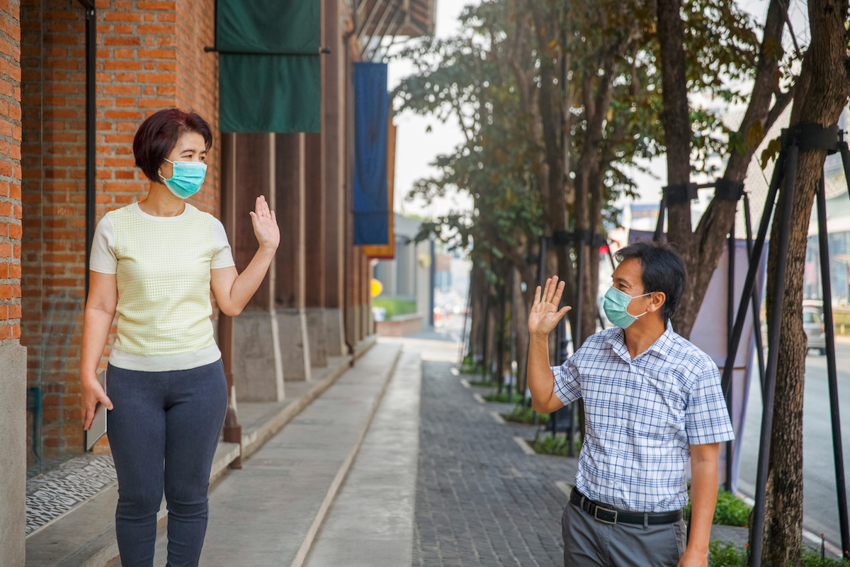 Asian middle aged people wearing mask and keep social distancing to avoid the spread of COVID-19