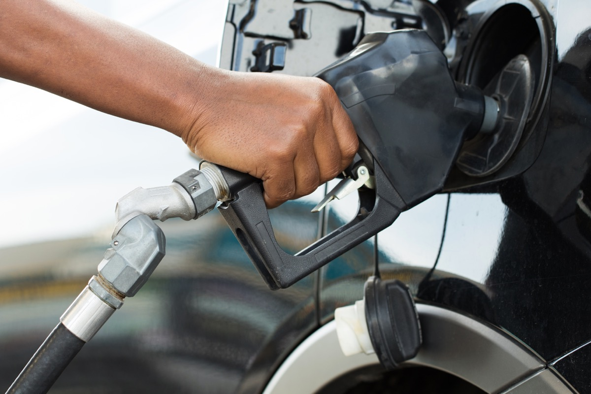 Person putting gas in car