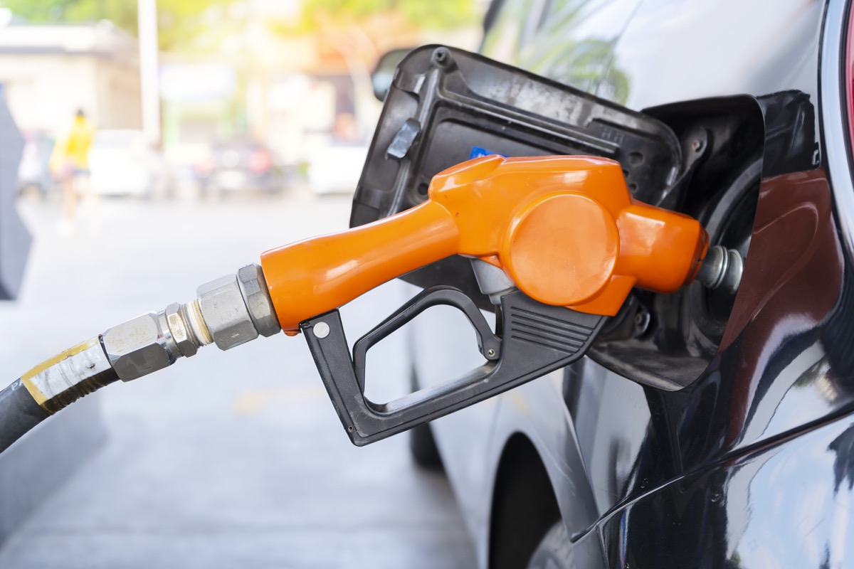 fuel nozzle filled car with fuel, car being filled gasoline at gas station, Pumping gasoline fuel in black car at gas station , Gas pump nozzle.