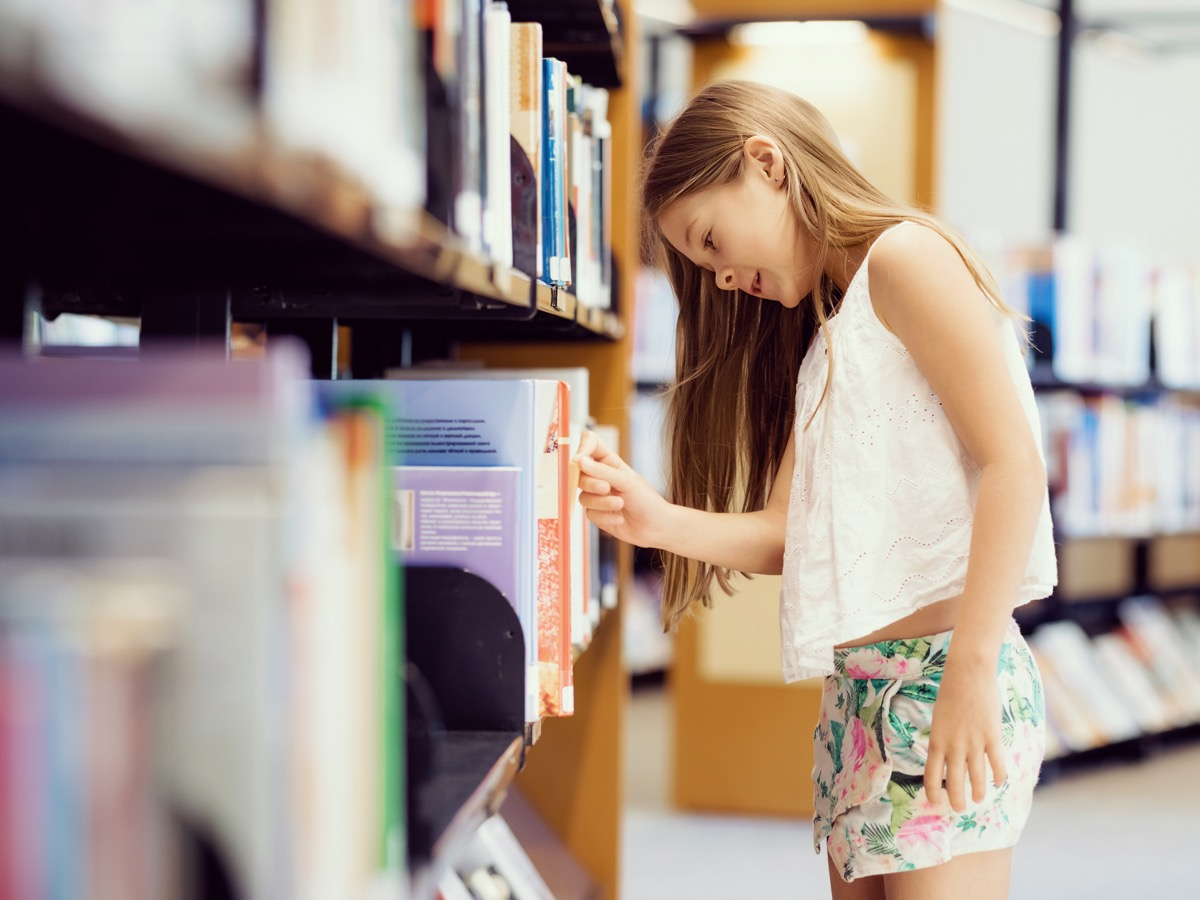 young white girl taking book out of library