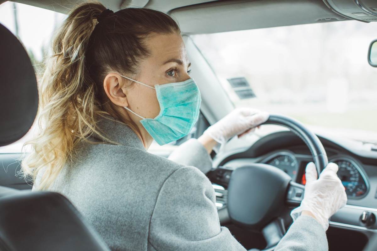 Woman during pandemic isolation at city, she is in car