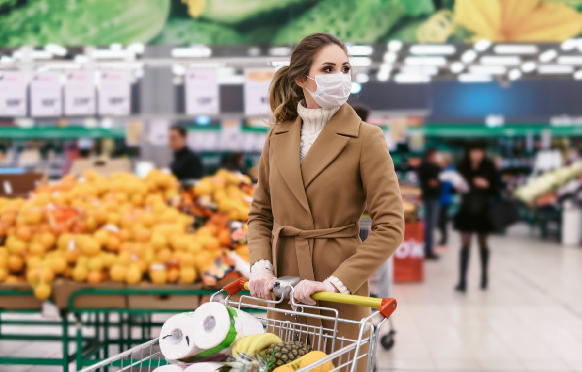 a woman goes grocery shopping with a mask