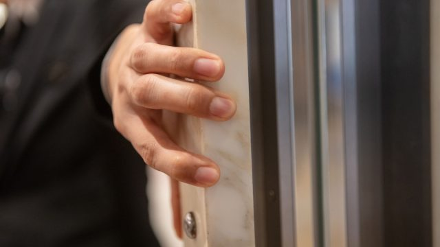 Close-up of unrecognizable person holding elevator door