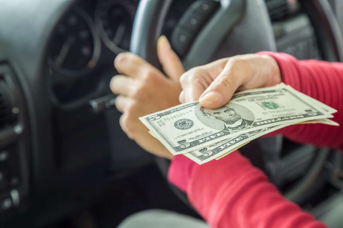 Driver gives dollars to policeman for road traffic offenses. Bribery.