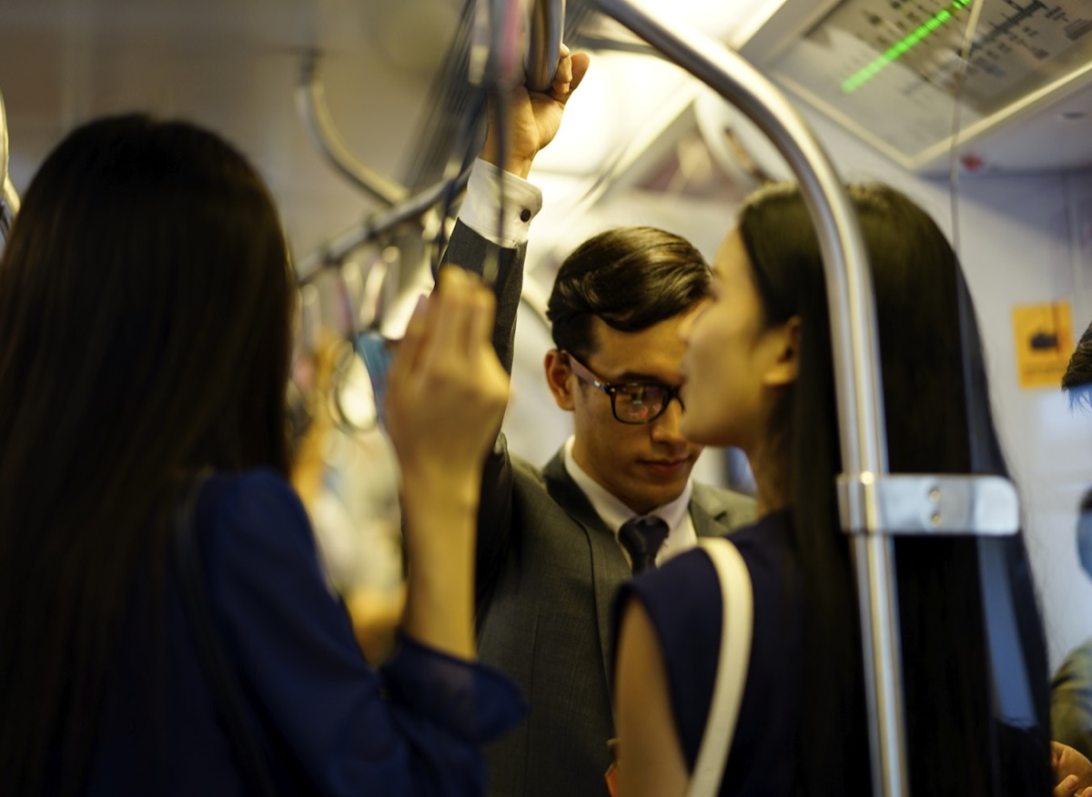 young asian people handing onto public transportation railing