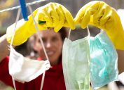 Adult Woman Recycling Disposable Face Masks Due to Shortage of Protective Masks during COVID-19 Pandemic