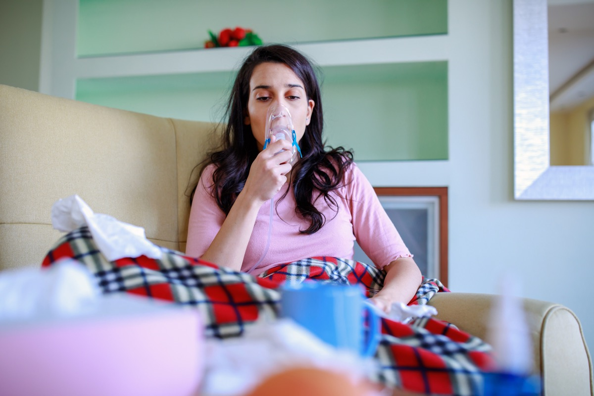 A young woman is suffering from problems with the respiratory system. A beautiful woman with long hair is suffering from pneumonia and using a smoke inhaler at home while sitting on the sofa-COVID-19, (A young woman is suffering from problems with the