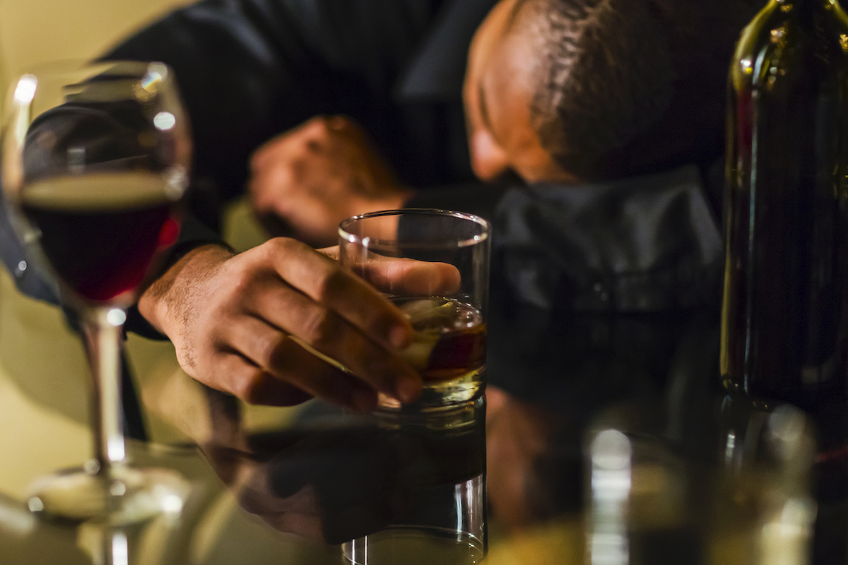 Drunk man with alcohol sleeping on table