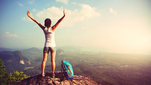 Woman at the top of a mountain on a hike