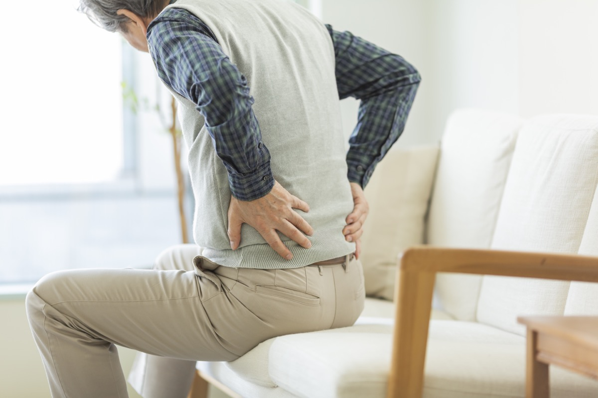 man with hip pain holding his back