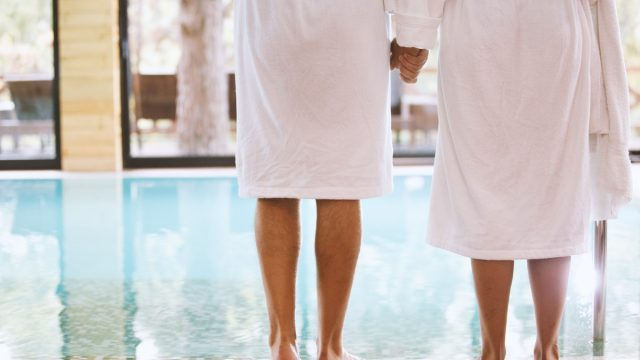 Rear view of man and woman standing on poolside barefoot, holding hands. They are wearing white bathrobes.