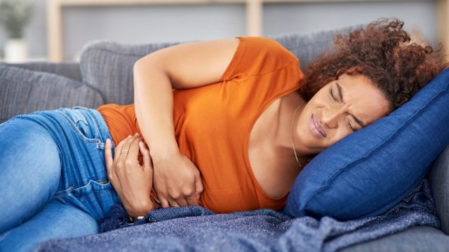 young woman clutching her stomach in pain while lying on the couch