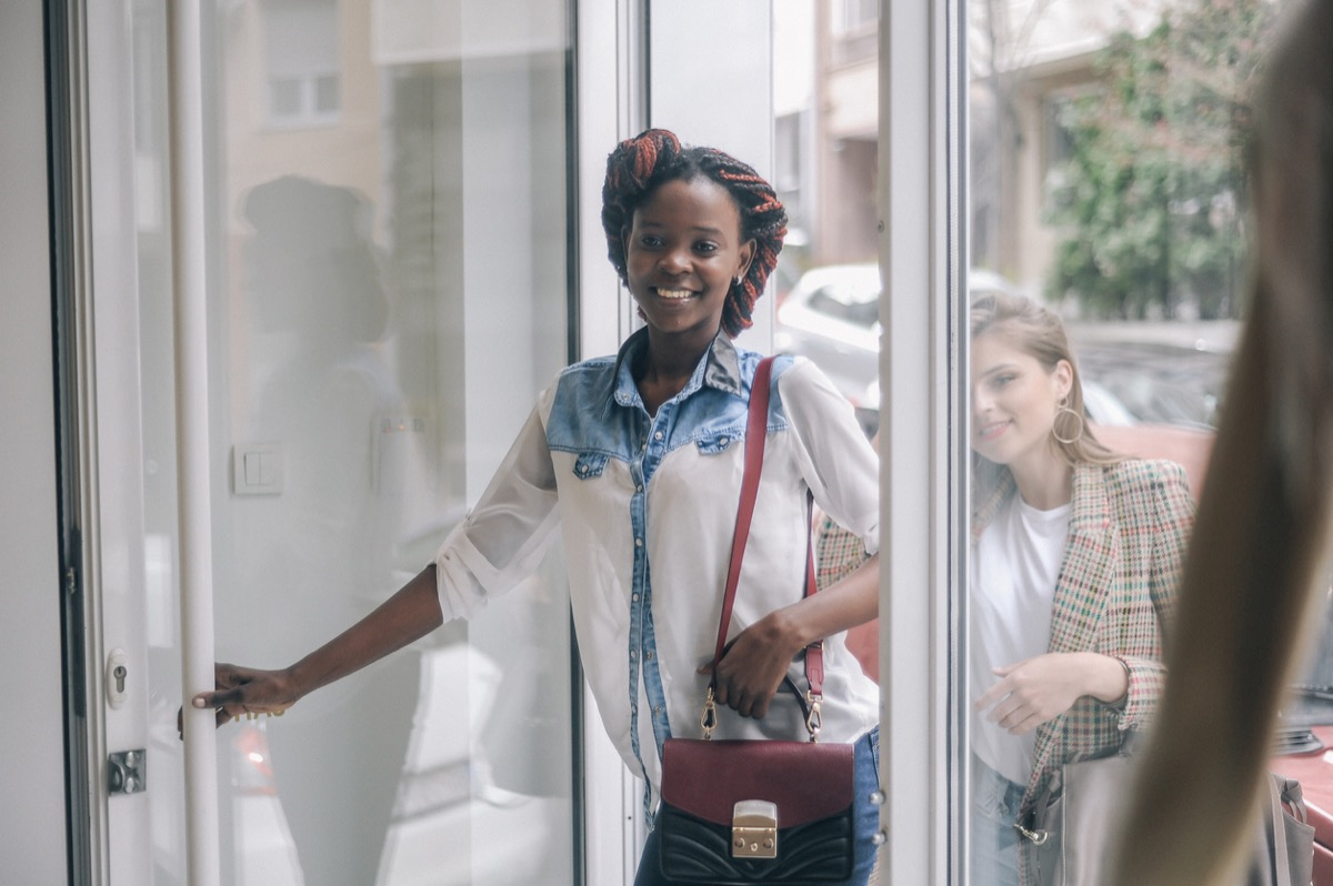 black woman opening the door and entering a store with a white woman standing behind her