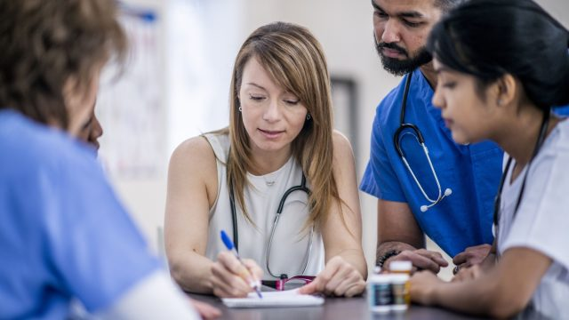 a group of multiethnic doctors looking over forms