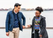 asian man and black woman talking outside by the water