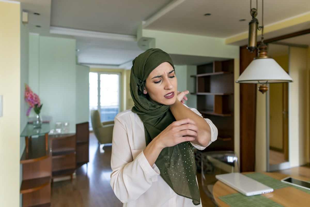 young muslim woman scratching her elbow