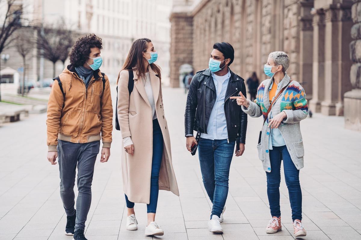 four friends wearing face masks walking down a city street