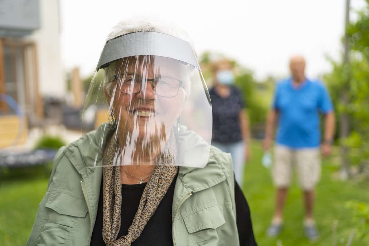 older white woman smiling behind a face shield outside