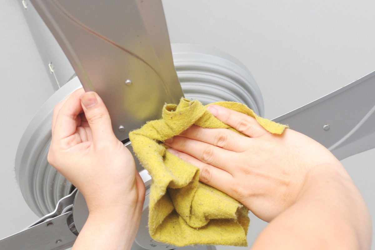 close up of hands wiping down ceiling fan