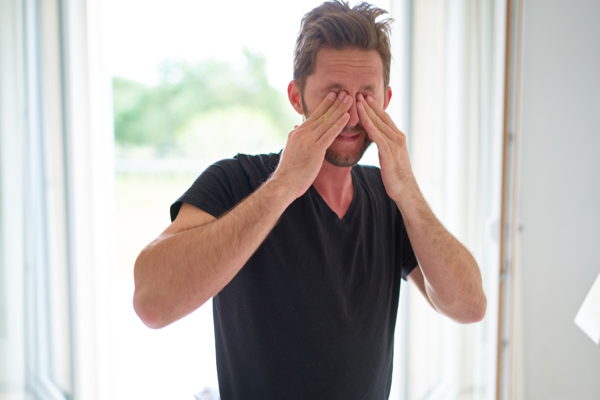 young white man rubbing his eyes inside