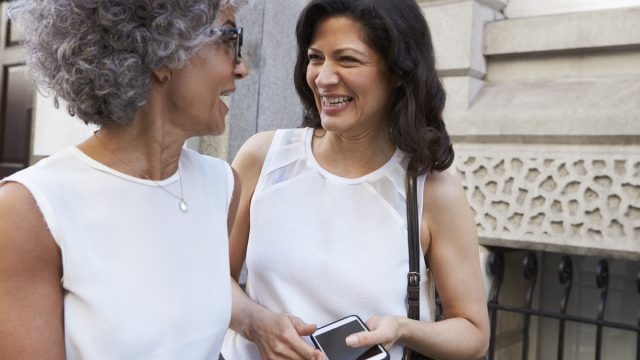 two older women talking close together on the street