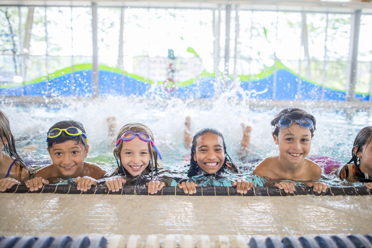 group of kids are taking a swimming class at an indoor pool. They are practicing kicking at the side of the pool, while smiling at the camera.