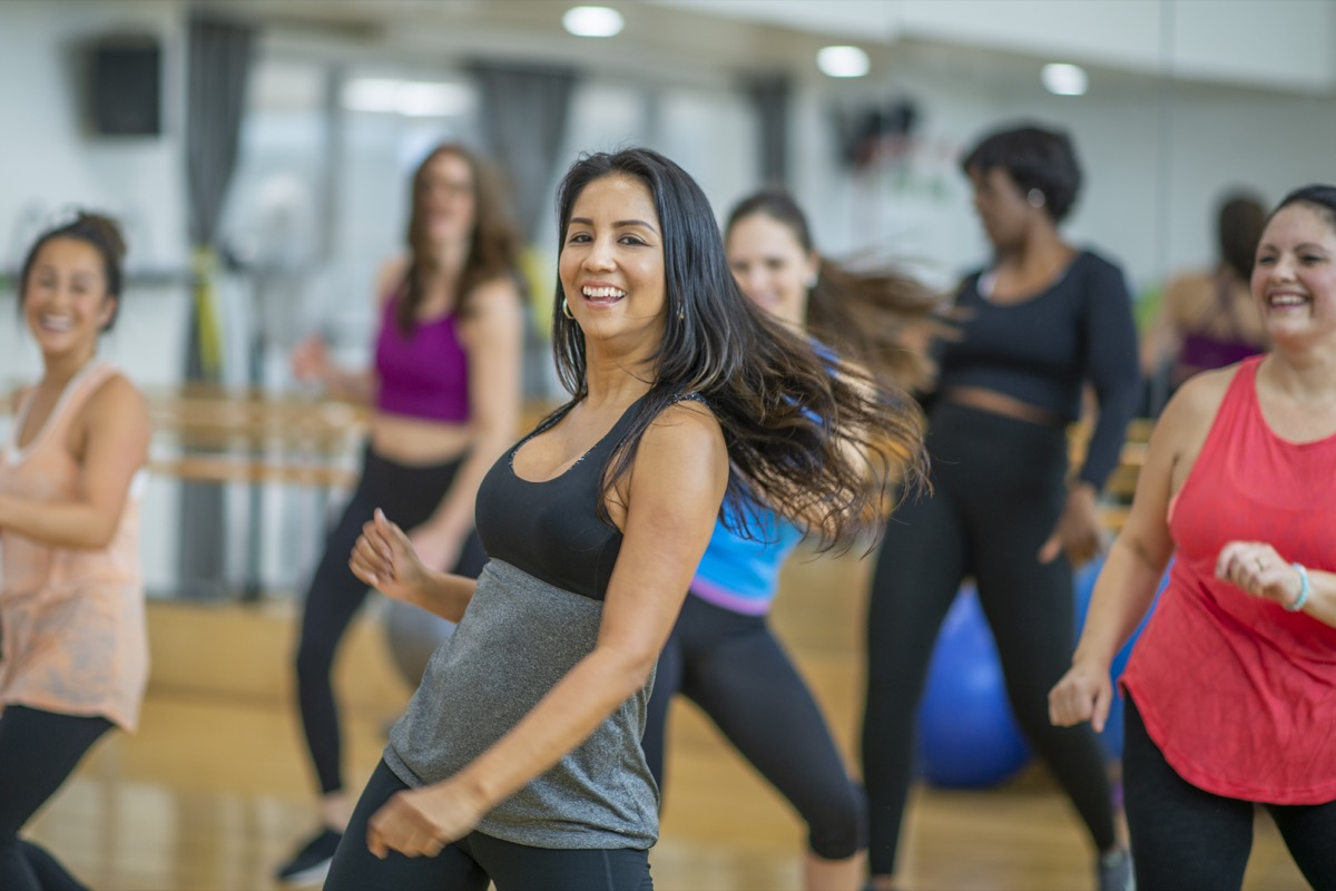 A group of adult women are dancing in a fitness studio. They are wearing athletic clothes. An Ethnic woman is smiling while dancing in the foreground.
